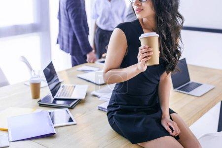 Photo pour Vue partielle de la femme afro-américaine avec café pour aller et collègues derrière au bureau - image libre de droit