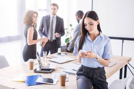 Photo pour Mise au point sélective de femme d'affaires asiatique à l'aide de smartphone et ses collègues derrière au bureau - image libre de droit