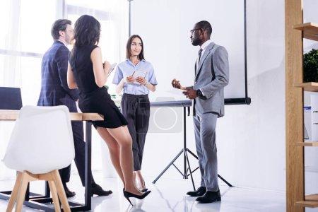 Photo pour Groupe multi-ethnique de gens d'affaires vêtements discutant projet ensemble au bureau - image libre de droit