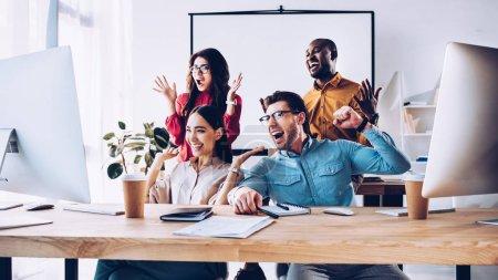 Photo pour Heureuse équipe multiraciale d'affaires travaillant sur le projet ensemble dans le bureau - image libre de droit