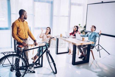 Photo pour Des affaires multiculturelles personnes voeux africaine collègue américain à vélo au bureau - image libre de droit