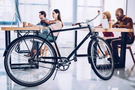 Photo pour Vue latérale du vélo et des gens d'affaires multiculturelles au bureau - image libre de droit