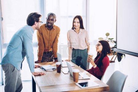 Photo pour Interracial groupe de collègues de travail, discuter de travail pendant la pause café au lieu de travail au bureau - image libre de droit