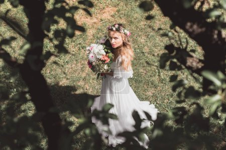 high angle view of beautiful young bride holding bouquet of flowers and looking at camera outdoors