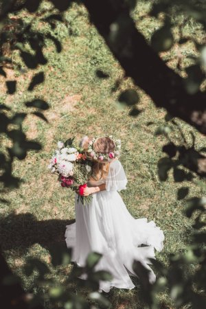 selective focus of beautiful young bride holding bouquet of flowers in park
