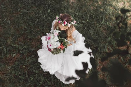 top view of beautiful young bride in wedding dress and floral wreath holding bouquet of flowers outdoors