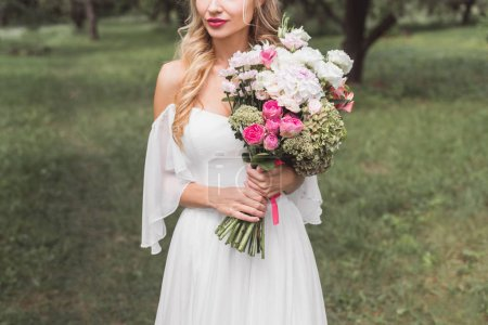 cropped shot of beautiful tender young bride holding wedding bouquet outdoors