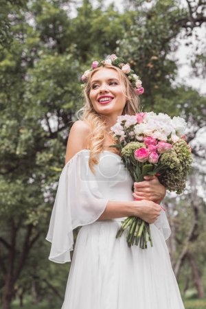 low angle view of smiling young bride in floral wreath holding wedding bouquet and looking away outdoors