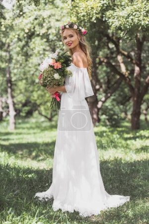 beautiful young bride in wedding dress holding bouquet of flowers and smiling at camera outdoors