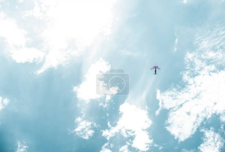 bottom view of airplane flying in blue sky with white clouds