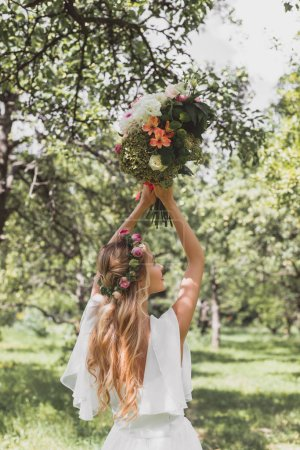 back view of beautiful young bride throwing wedding bouquet in park