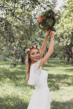 beautiful smiling young bride throwing wedding bouquet in park