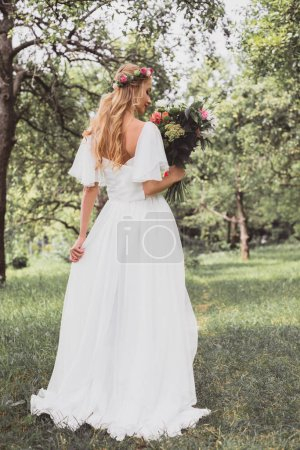 back view of beautiful young bride holding wedding bouquet in park