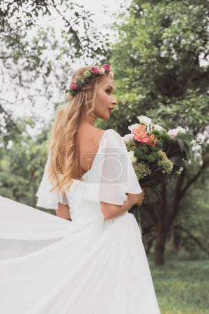 beautiful blonde bride in wedding dress and floral wreath holding bouquet of flowers in park