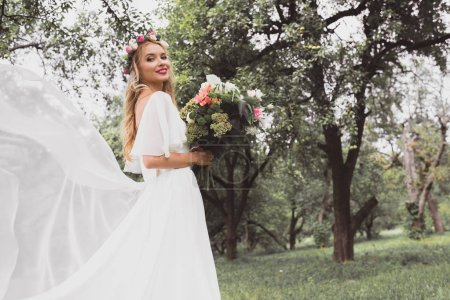 happy blonde bride in wedding dress and floral wreath holding bouquet and smiling at camera in park