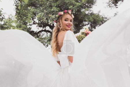 low angle view of happy blonde bride in wedding dress and floral wreath smiling at camera in park