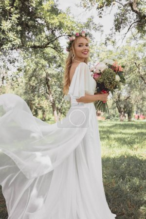 beautiful young bride in wedding dress holding bouquet of flowers and smiling at camera in park