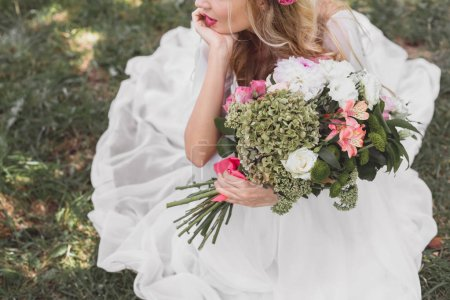 cropped shot of thoughtful young bride holding bouquet of flowers outdoors
