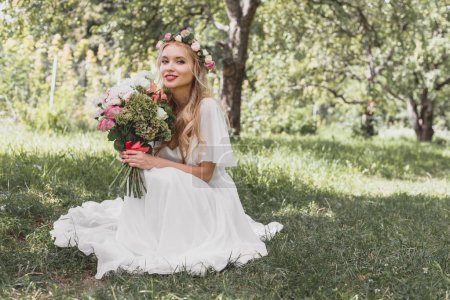 beautiful young blonde bride holding wedding bouquet and smiling at camera in park