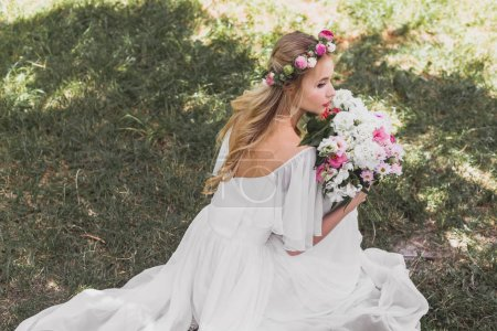 high angle view of beautiful young bride in wedding dress holding bouquet of flowers and looking away in park