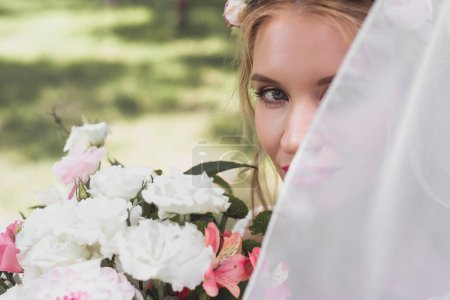 beautiful young bride in veil holding bouquet of flowers and looking at camera