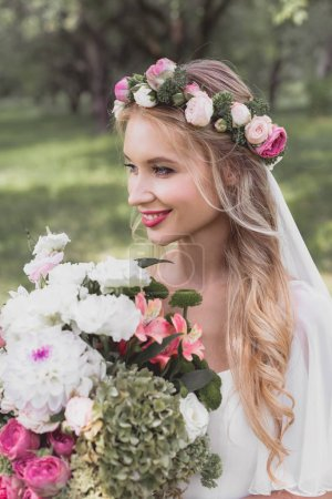 beautiful smiling young bride in floral wreath and veil holding bouquet and looking away