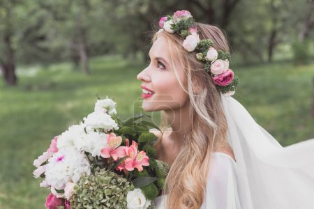 side view of beautiful tender bride holding bouquet of flowers and looking up in park