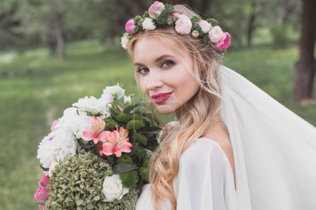 beautiful young bride in floral wreath and veil holding bouquet and smiling at camera