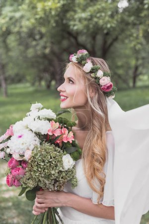 side view of beautiful smiling young bride in veil holding wedding bouquet and looking up