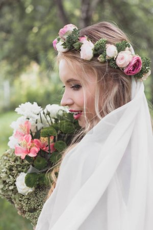 close-up view of beautiful smiling young bride in veil holding wedding bouquet