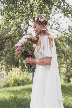 side view of smiling young bride holding wedding bouquet in park