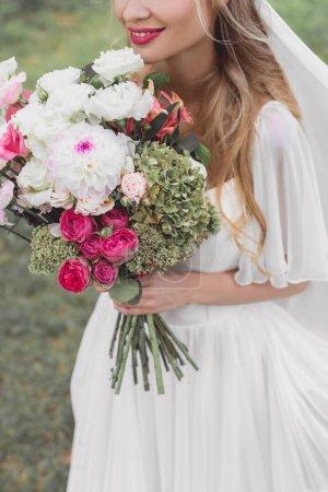 recadrée tir de sourire jeune mariée tenant le bouquet de fleurs à l'extérieur