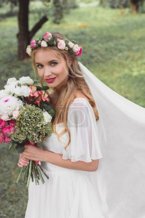 high angle view of beautiful young bride holding wedding bouquet and smiling at camera outdoors