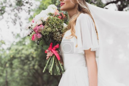 cropped shot of young bride in wedding dress and veil holding beautiful bouquet of flowers