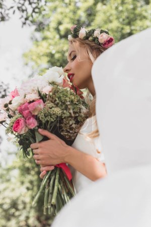 low angle view of tender young bride in floral wreath and veil holding wedding bouquet outdoors