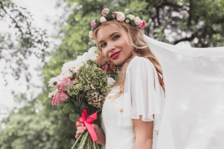 low angle view of beautiful blonde bride in floral wreath and veil holding wedding bouquet and smiling at camera