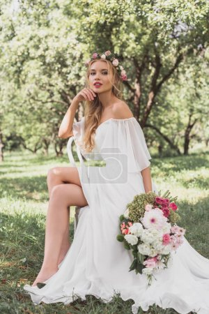 beautiful young bride in floral wreath and wedding dress sitting on chair and looking at camera outdoors