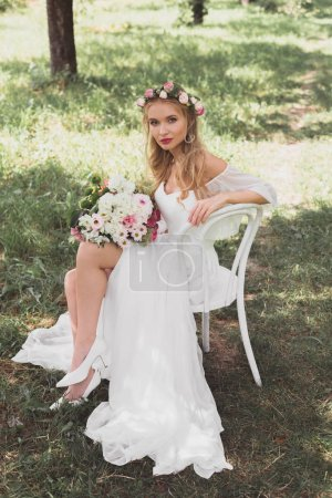 high angle view of beautiful young bride sitting on chair and looking at camera outdoors