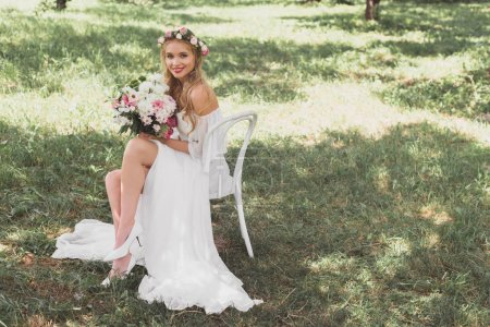 high angle view of happy young bride holding bouquet of flowers and smiling at camera while sitting on chair outdoors