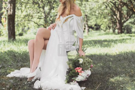 cropped shot of young blonde bride holding wedding bouquet and sitting on chair outdoors