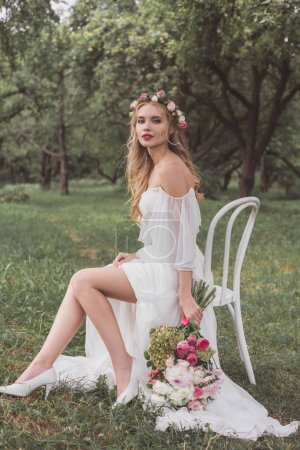 beautiful young bride with wedding bouquet sitting on chair and smiling at camera in park
