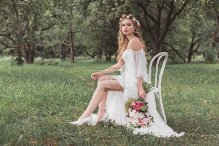 beautiful young bride with wedding bouquet sitting on chair and looking at camera in park