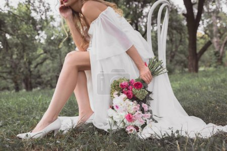 cropped shot of young bride holding bouquet of flowers and sitting on chair in park