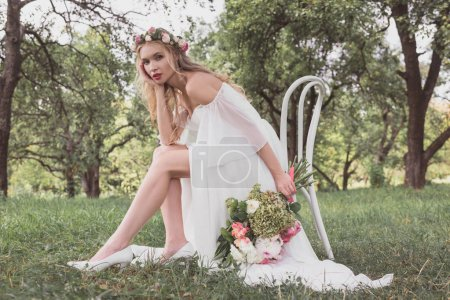 beautiful young bride holding wedding bouquet and looking at camera while sitting on chair in park