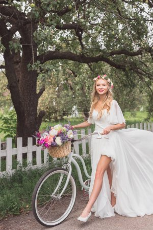 beautiful young bride walking with bicycle and smiling at camera