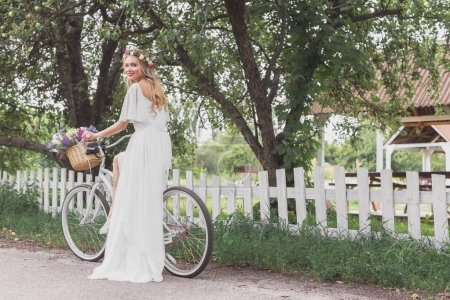 beautiful young bride in wedding dress riding bicycle and smiling at camera