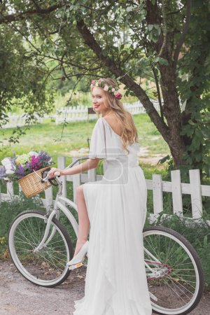 beautiful smiling young bride in wedding dress riding bicycle