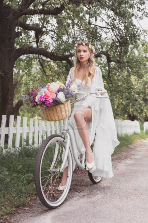 beautiful young blonde bride riding bicycle with flower basket