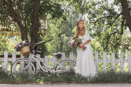 beautiful young bride with wedding bouquet and bicycle standing near fence and looking away