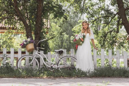 beautiful young bride holding bouquet and smiling at camera while standing near bicycle at fence